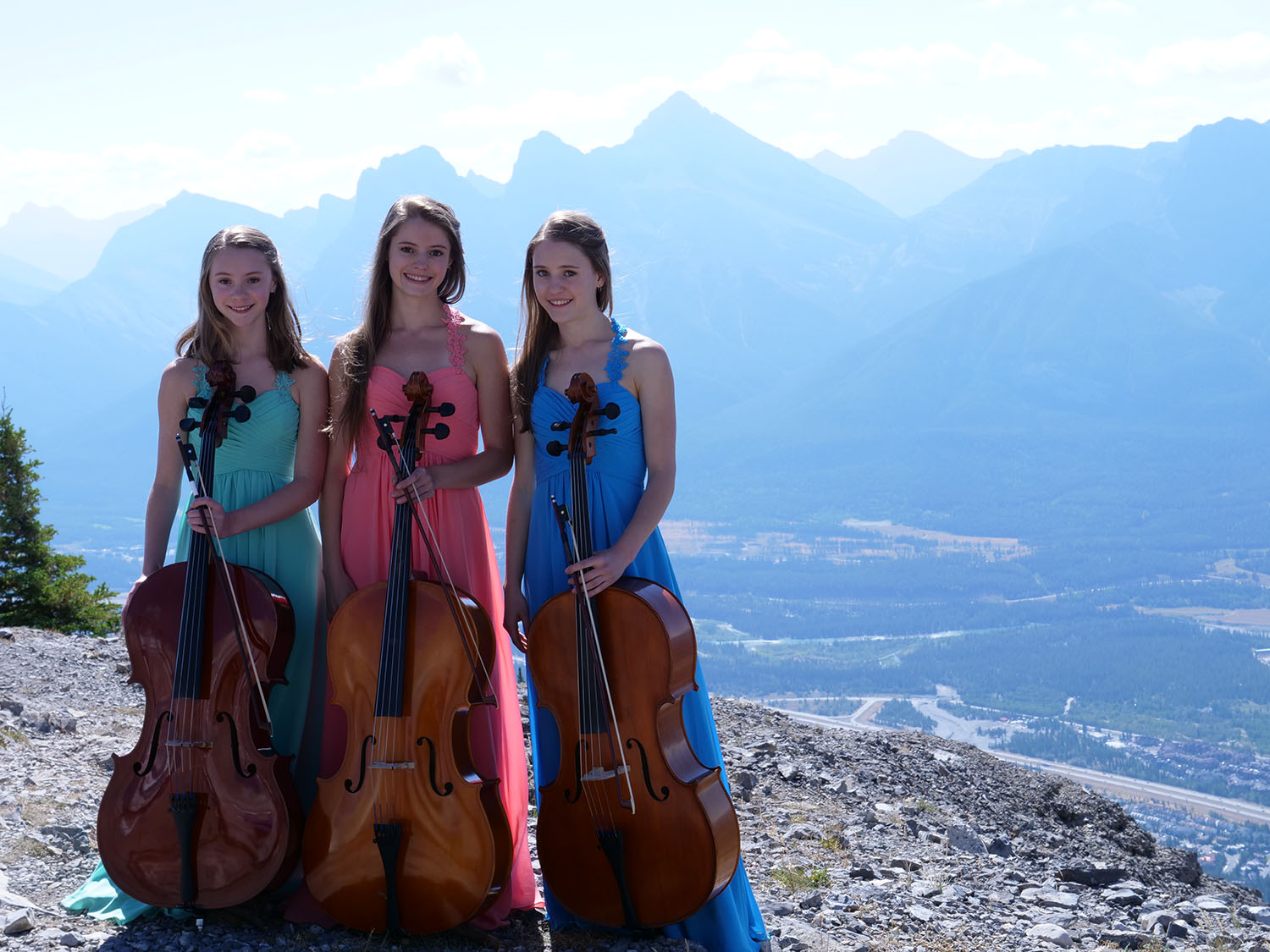 Luka, Ine and Mari Coetzee are the Three Sisters cello trio, pictured in front of the Three Sisters mountain peaks near Canmore, Alberta.